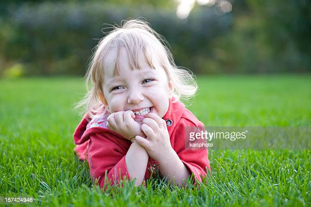 Smiling girl in pink lying with belly on the green grass