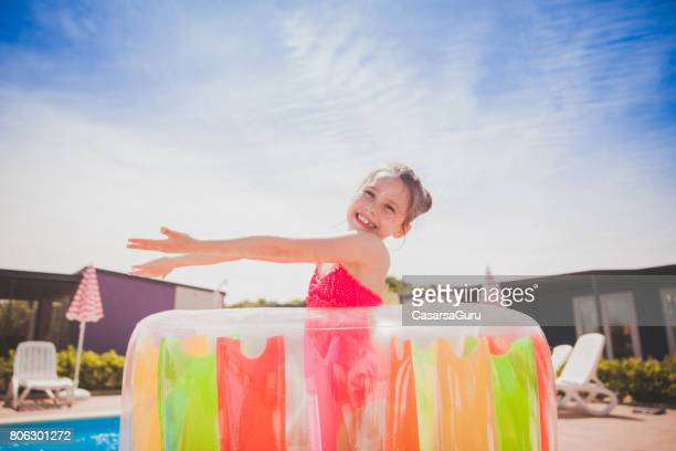Smiling Girl Inside The Inflatable Whater Wheel Near The Swimming Pool