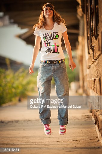 Smiling girl jumping for joy outdoors : ストックフォト