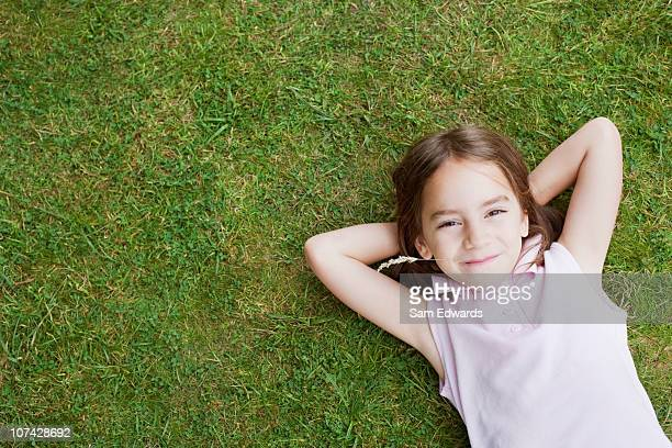 Smiling girl laying in grass chewing weed