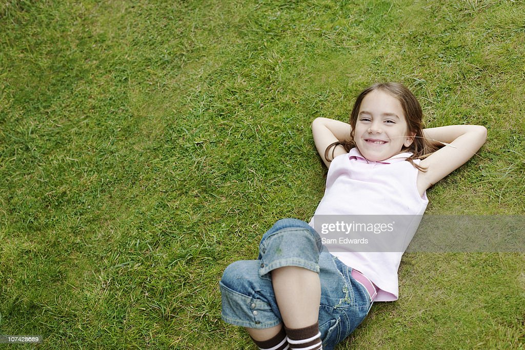 Smiling girl laying in grass : Stock Photo