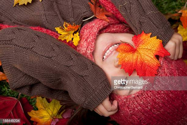 Smiling girl laying on autumn leaves