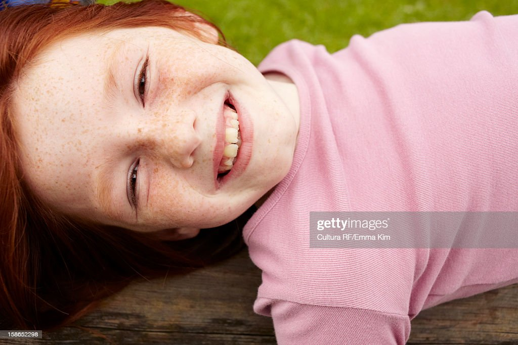 Smiling girl laying on wooden log : Stock Photo