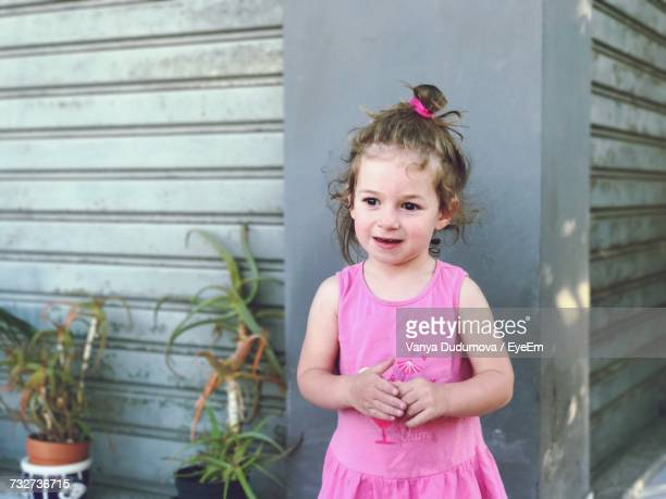 Smiling Girl Looking Away While Standing By Building