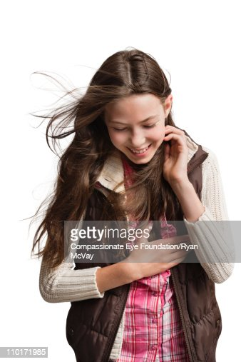 Smiling girl looking down and holding her hair : Stock Photo