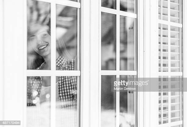 Smiling girl looking through the window