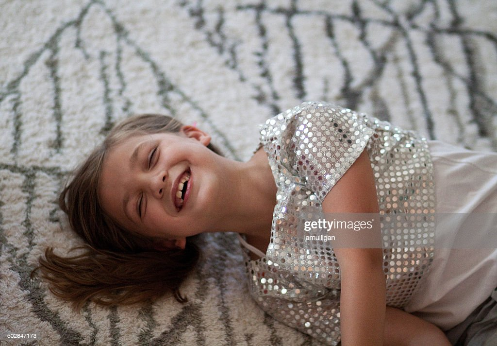 Girl (6-7) lying on carpet