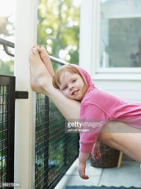 Smiling girl lying on mother legs