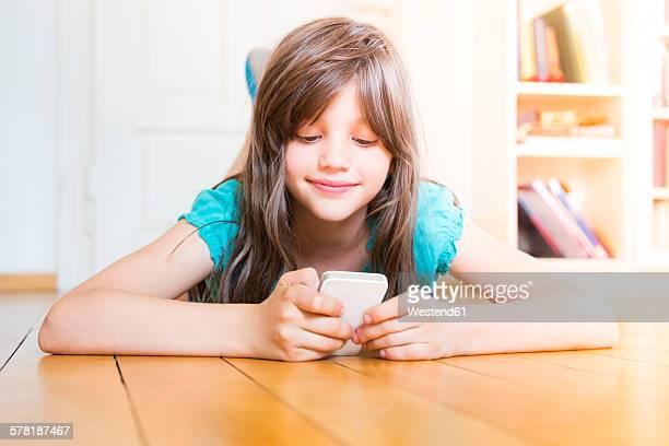 Smiling girl lying on wooden floor using smartphone