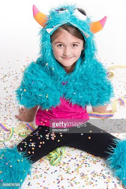 Smiling girl masquerade as a monster sitting on white ground covered with confetti