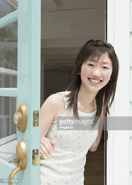 Smiling girl opening the door