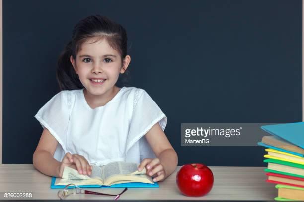 Jeune fille souriante ouvre le livre devant la Commission scolaire