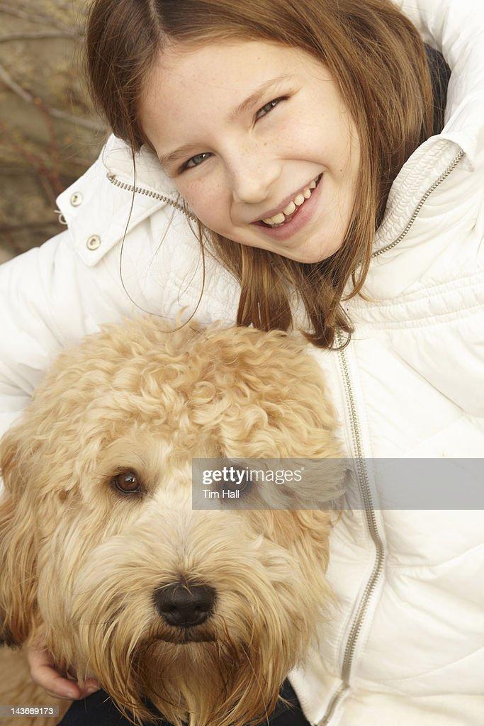 Smiling girl petting dog outdoors : Stock Photo