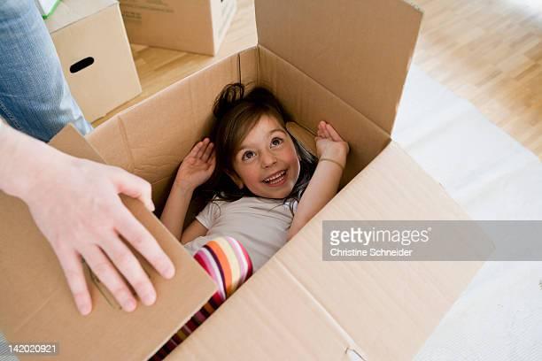 Smiling girl playing in cardboard box