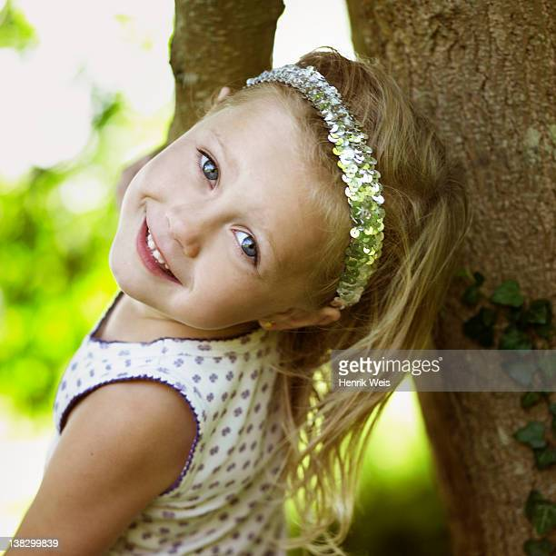 Smiling girl playing in tree