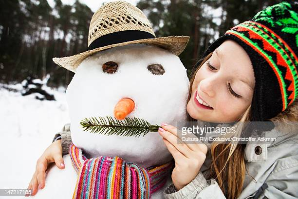 Smiling girl playing with snowman