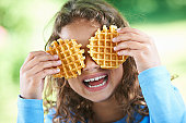 Smiling girl playing with waffles