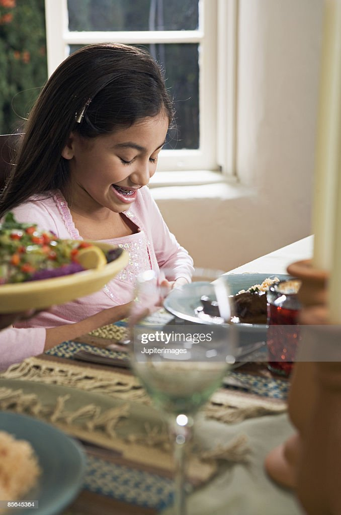 Smiling girl seated at dining table : Stock Photo