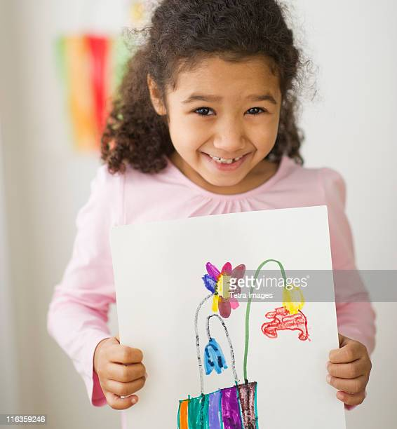 Smiling girl (6-7) showing her drawing