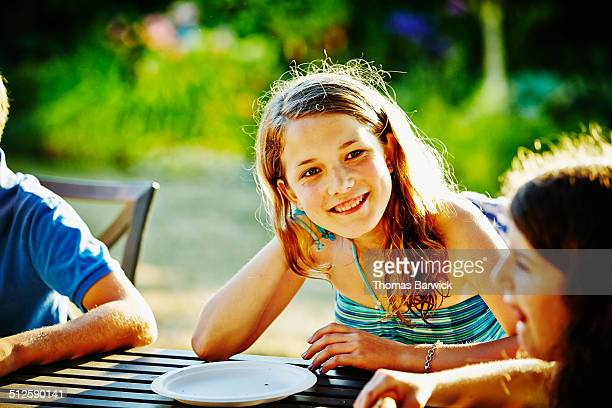Smiling girl sitting at table in backyard of home