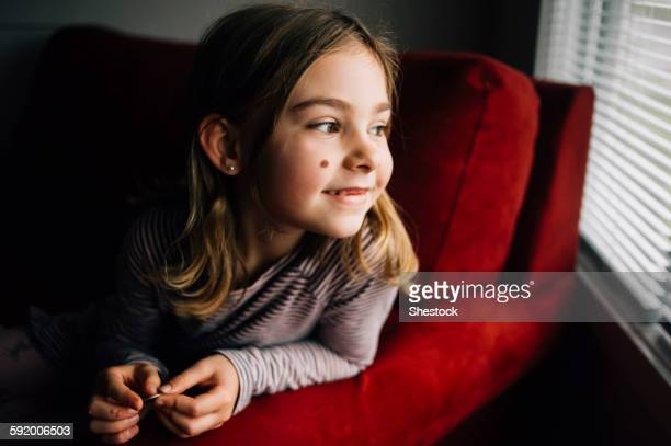 Smiling girl sitting in armchair