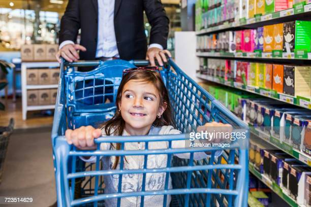 Smiling girl sitting in cart with father in supermarket