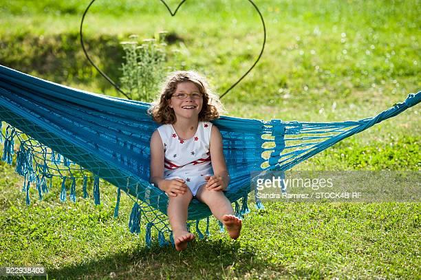 Smiling girl sitting in hammock