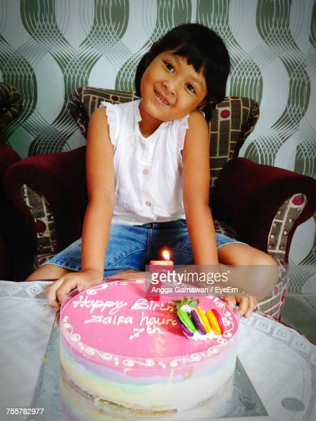 Smiling Girl Sitting On Armchair By Birthday Cake
