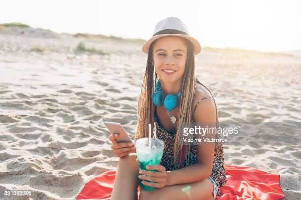 Jeune fille souriante assise sur la plage et buvant cocktail vert