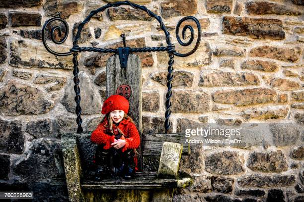 Smiling Girl Sitting On Bench Against Stone Wall During Sunny Day
