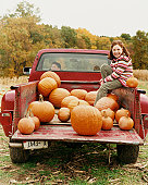 Smiling Girl Sitting on Pick up Truck, Boy Sitting in Front
