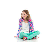 Happy little girl sitting on the floor with legs crossed and looking away. Full length studio shot isolated on white.