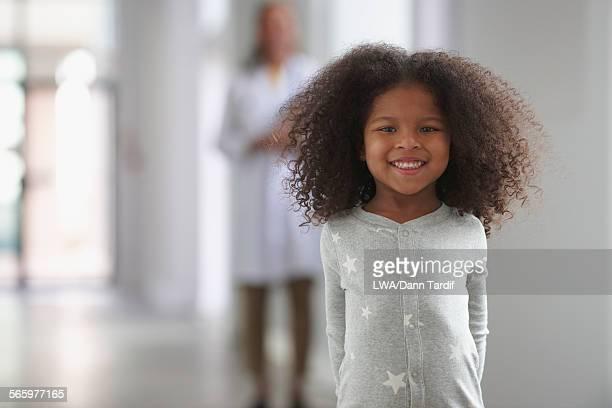Smiling girl standing in hospital hallway
