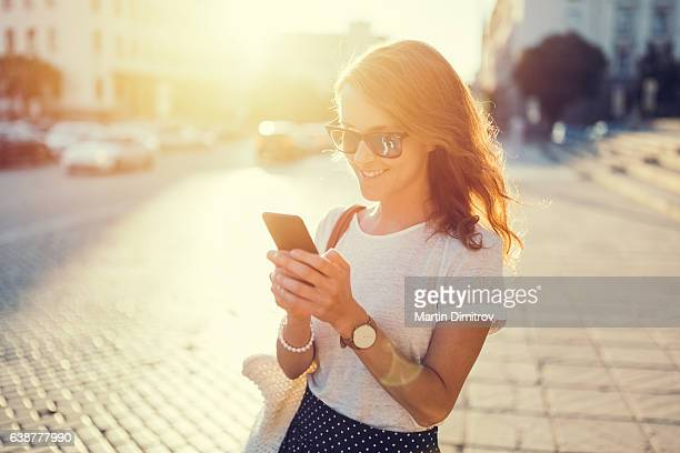 Smiling girl texting outside