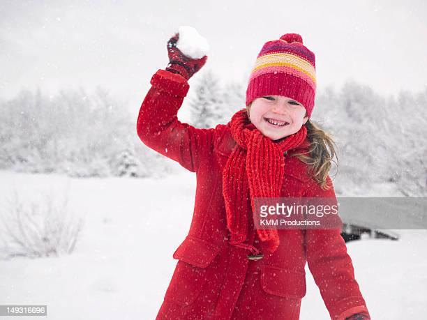 Smiling girl throwing snowball