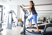 Smiling young attractive woman wearing sportswear and training on stair stepper in gym. Side view.