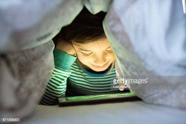 Smiling girl using digital tablet at home