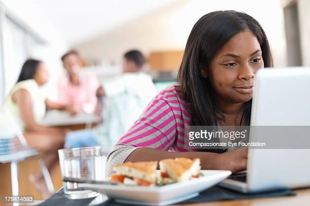 Smiling girl (12-13) using laptop in kitchen