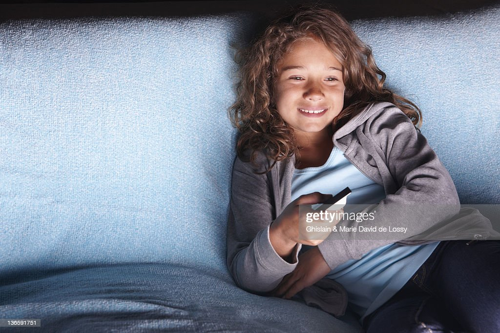 Smiling girl watching television on sofa : Stock Photo