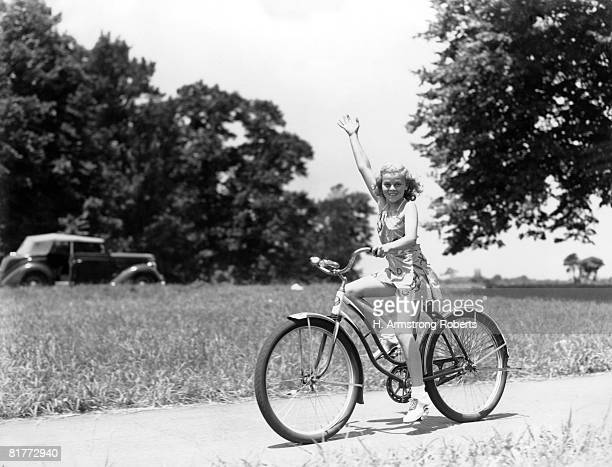 Smiling Girl Wearing A Jumper Short Set & Saddle Shoes Waving As She Is Riding Her Two Wheeler With Field Trees & Convertible Car In Background.