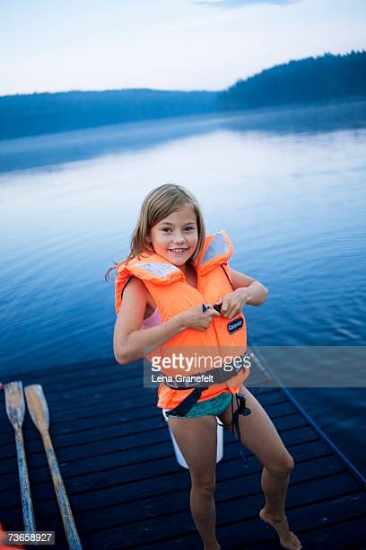 A smiling girl wearing a life jacket.