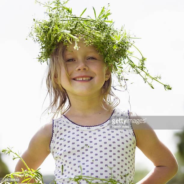 Smiling girl wearing grassy crown