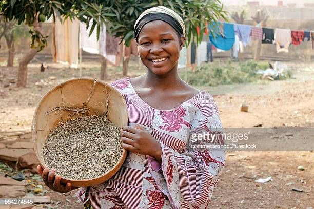 A smiling girl with a calabash of millet