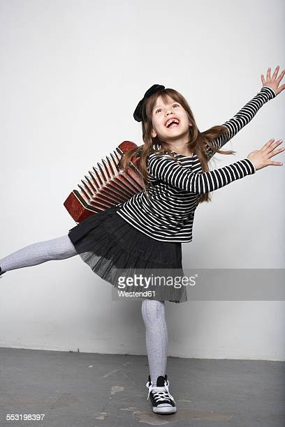 Smiling girl with accordion standing on one leg