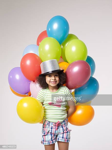 Smiling girl with balloons wearing top hat