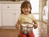 Smiling girl with basket of eggs