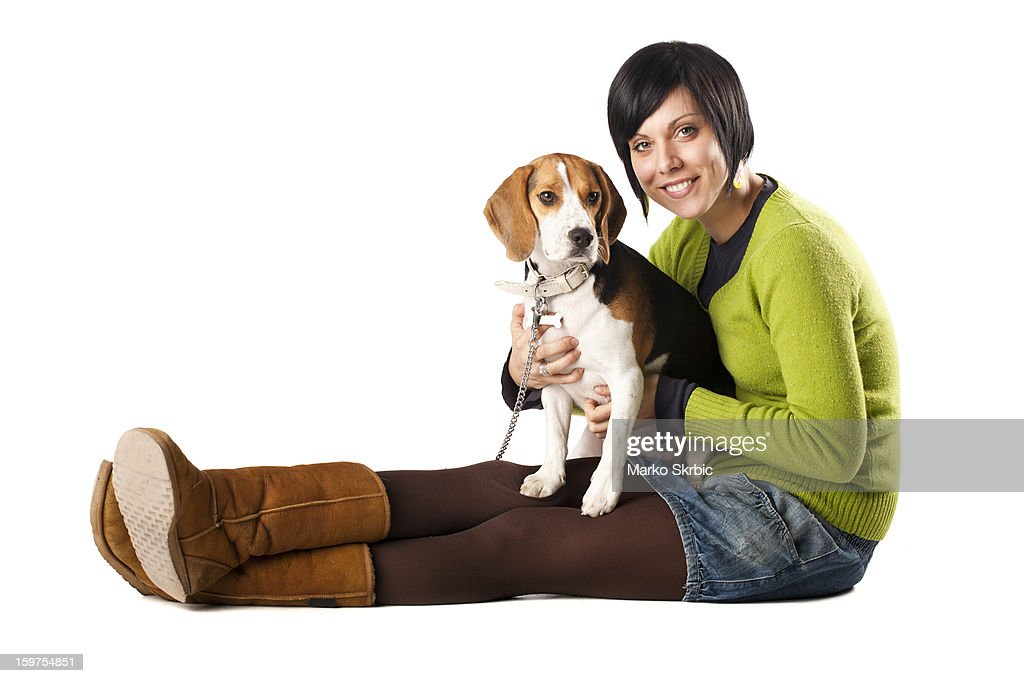 Smiling girl with Beagle dog in her lap : Stock Photo