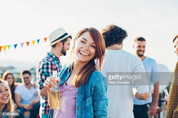 Smiling girl with beer bottle on a party