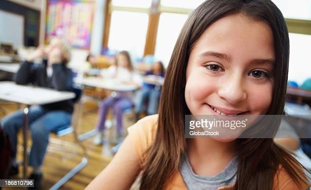 Lächelnd Mädchen mit Klassenkameraden im Hintergrund