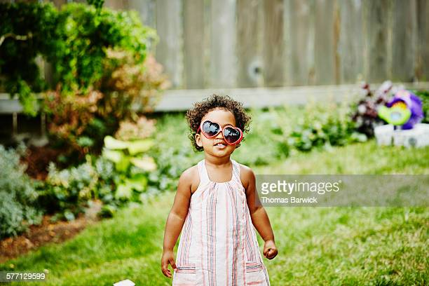 Smiling girl with crooked sunglasses on face